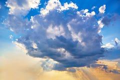 Лучи ` s солнца делают их путь через огромное облако кумулюса Стоковое Изображение