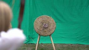 Лучник держит его смычок и стрелку всходов на цели Конкуренция Archery, люди направляя в центр цели выиграть приз Outd видеоматериал