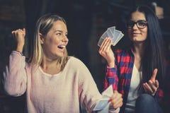 2 лучшего друга играя карточки игры дома стоковая фотография
