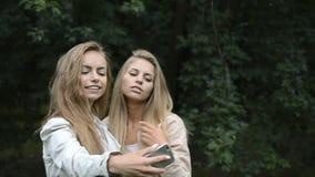 2 лучшего друга красивые маленькая девочка или женщина принимая selfie видеоматериал