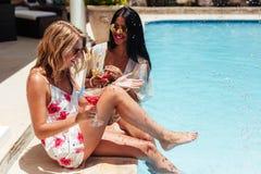 Лучшие други наслаждаясь на poolside курорта стоковые фотографии rf