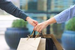 Лучшие други, 2 предназначенных для подростков девушки вручают удержание хозяйственных сумок с положением на универмаге стоковое фото rf