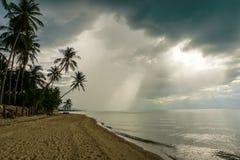 Луч светы идут через облака тропическим пляжем Стоковое Изображение