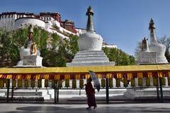 ЛХАСА, АВТОНОМНАЯ ОБЛАСТЬ ТИБЕТА, КИТАЙ - ОКОЛО МАЙ 2018: Монах с парасолем идя вдоль тибетских колес молитве, дворца Potala стоковые изображения rf