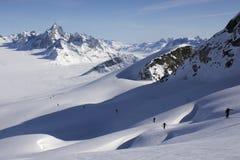 Лыжа взбираясь на crevassed наклоне и бесконечном ледниковом пейзаже. Стоковое Изображение