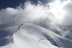 Лыжники взбираясь снежная гора Стоковое Изображение