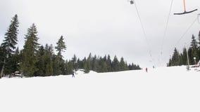 Лыжники используя анкер подъема лыжи на горе Люди двигая медленно гор сток-видео
