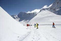 Лыжники идя вниз с наклона на лыжном курорте Стоковое Изображение RF