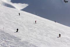 Лыжники идя вниз с наклона на лыжном курорте Стоковые Изображения RF