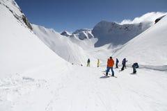 Лыжники идя вниз с наклона на лыжном курорте Стоковые Фото