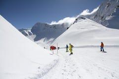 Лыжники идя вниз с наклона на лыжном курорте Стоковые Изображения
