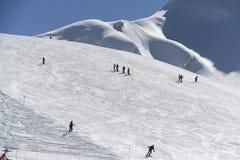 Лыжники идя вниз с наклона на лыжном курорте Стоковое фото RF