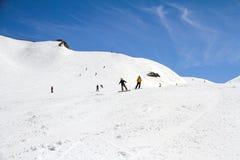 Лыжники идя вниз с наклона на лыжном курорте Стоковое Фото