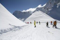 Лыжники идя вниз с наклона на лыжном курорте Стоковая Фотография