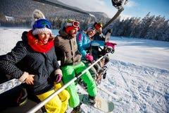 Лыжники и snowboarders друзей наслаждаясь в наклонах на зиме Стоковое Фото