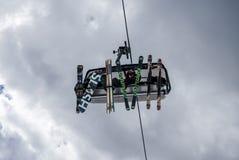Лыжники и snowboarders используя подъем лыжи в популярном лыжном курорте Стоковые Фото