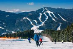 Лыжники и snowboarders идя вниз с наклона на лыжном курорте Стоковое Фото