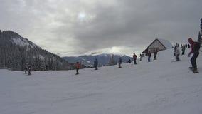 Лыжники и snowboarders идя вниз видеоматериал