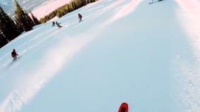 Лыжники катаясь на лыжах вниз со снежного холма видеоматериал