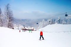 Лыжники катаясь на лыжах на лыжном курорте зима белизны снежинок предпосылки голубая Туризм Стоковое Изображение RF