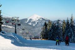 Лыжники на лыжном курорте на предпосылке подъема, леса, холмы Стоковое фото RF