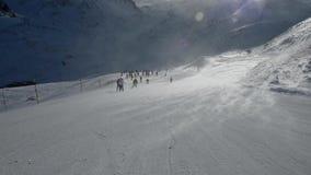 Лыжники на piste идя покатый в сильных ветерах сток-видео