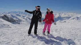 Лыжники показывают руке интересные места в долине горы сток-видео