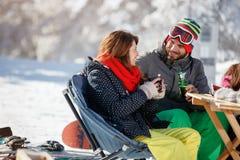 Лыжники соединяют выпивать и говорить в кафе на катании на лыжах Стоковое фото RF