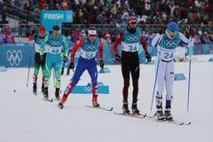 Лыжники состязаются на массовом старте в ` s 15km + 15km Skiathlon людей на 2018 Олимпийских Играх зимы Стоковая Фотография