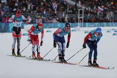 Лыжники состязаются на массовом старте в ` s 15km + 15km Skiathlon людей на 2018 Олимпийских Играх зимы Стоковые Фотографии RF