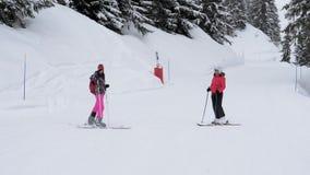 Лыжники стоя на одине другого выставки наклона трасса где к кататься на лыжах акции видеоматериалы