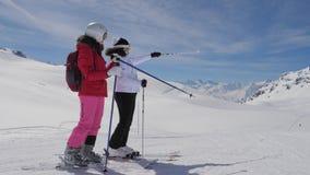 Лыжники увидели интересное в долине горы и одине другого выставки сток-видео