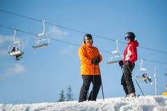 Лыжники человека и женщины с лыжами на зиме прибегают Стоковое фото RF