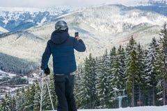 Лыжник в горах сфотографировал на мобильном телефоне beauti Стоковое Изображение