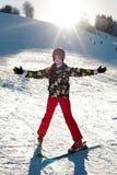Лыжник девушки в красных брюках и зеленой куртке на лыжах протягивая вне ее оружия счастливые с ` s солнца излучает Стоковое фото RF