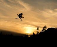 Лыжник делая самосхват с скачки в заходе солнца Стоковые Фотографии RF