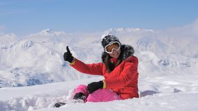 Лыжник женщины показывает о'кей и палец руки вверх на предпосылке гор Snowy стоковое изображение rf