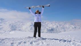 Лыжник женщины стоит на горе наклона, поднятой вверх лыже и развевает они стоковая фотография rf