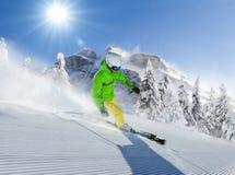 Лыжник молодого человека бежать вниз с наклона в высокогорные горы Стоковые Изображения