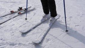 Лыжник надевает дальше его покатую лыжу белые ботинки лыжи стоковые фотографии rf