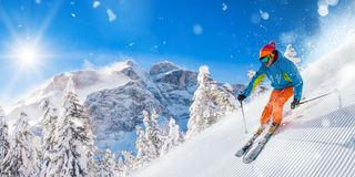 Лыжник на бежать piste покатый в красивом высокогорном ландшафте Голубое небо на предпосылке стоковое фото rf