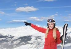 Лыжник на предпосылке снег-покрытых гор Привлекательная блондинка в красном костюме лыжи с сноубордом в руках показывает дальше стоковая фотография rf