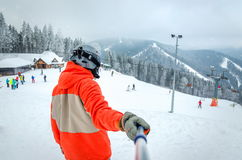 Лыжник нося шлем стоит с его задняя часть и смотреть горы Стоковые Изображения
