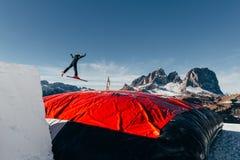 Лыжник скача на брыкунью, посадку воздушного шара, парк снега Val di Fassa Dolomiti Стоковое Фото