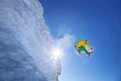 Лыжник скача против голубого неба от утеса Стоковое Изображение