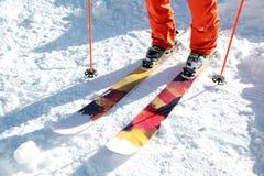 Лыжник спортсмена ног в апельсине общем на катании на лыжах спорта на снеге на солнечный день Концепция спорт зимы стоковые фото