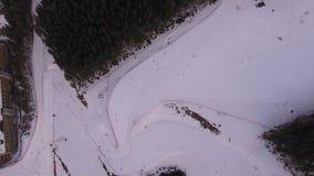 Лыжный курорт горы След для snowboarders След для лыжников Снимая следы сноуборда на верхней части Киносъемка от воздуха