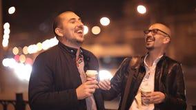 2 лысых друз идут в вечер в городе беседуя, выпивая кофе сток-видео