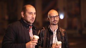 2 лысых друз идут в вечер в городе беседуя, выпивая кофе акции видеоматериалы