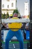 ЛЬВОВ, УКРАИНА - АВГУСТ 2017: Сильный спортсмен культурист поднимает огромный тяжелый каменный желтый шарик на игры сильных челов Стоковое Изображение